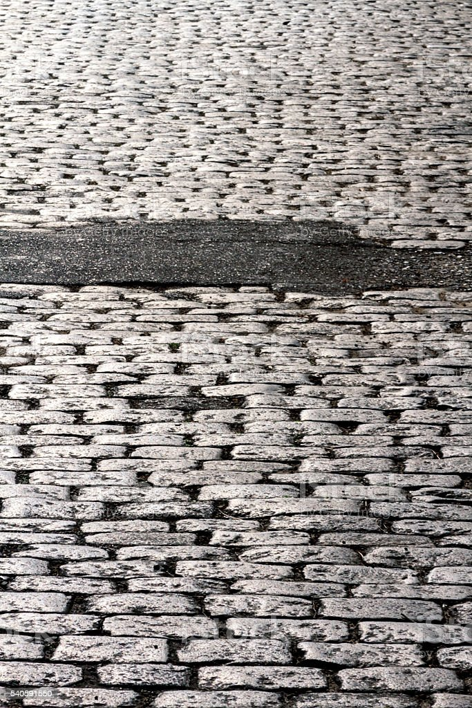 Cobbled street with asphalt patch stock photo