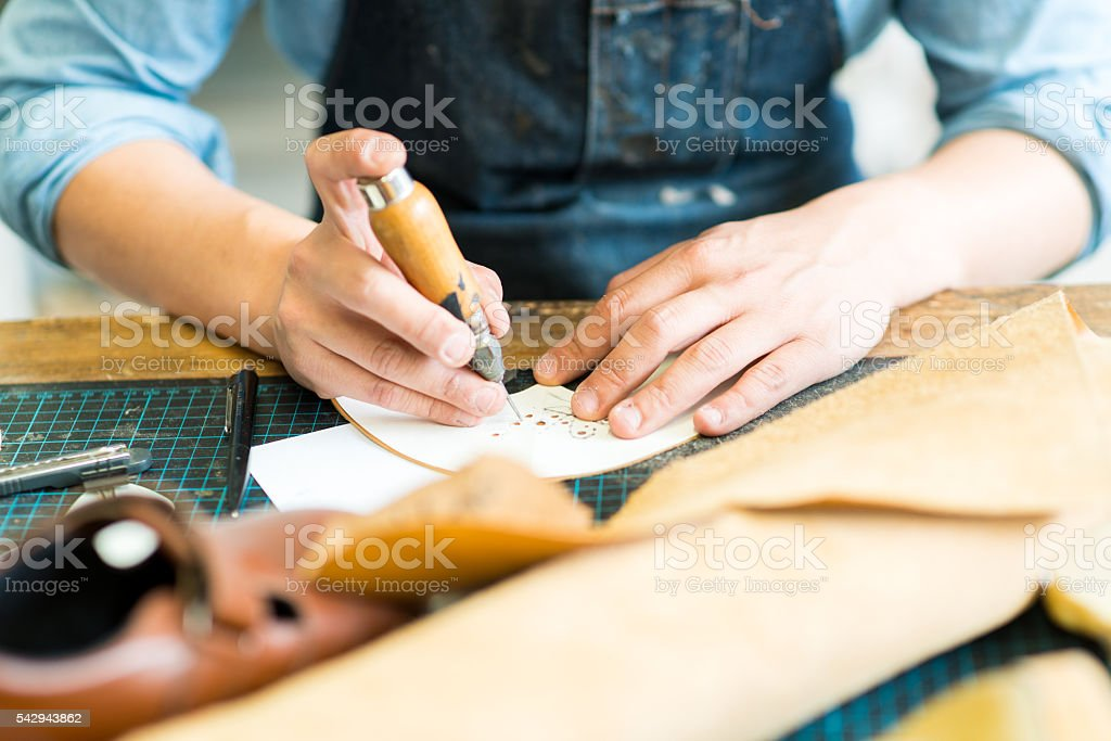Cobbler scoring holes in leather stock photo