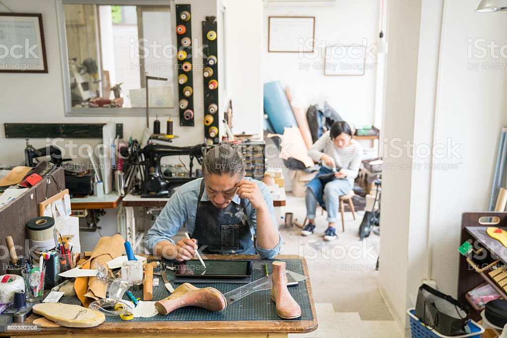 Cobbler using digital tablet in his traditional shop stock photo