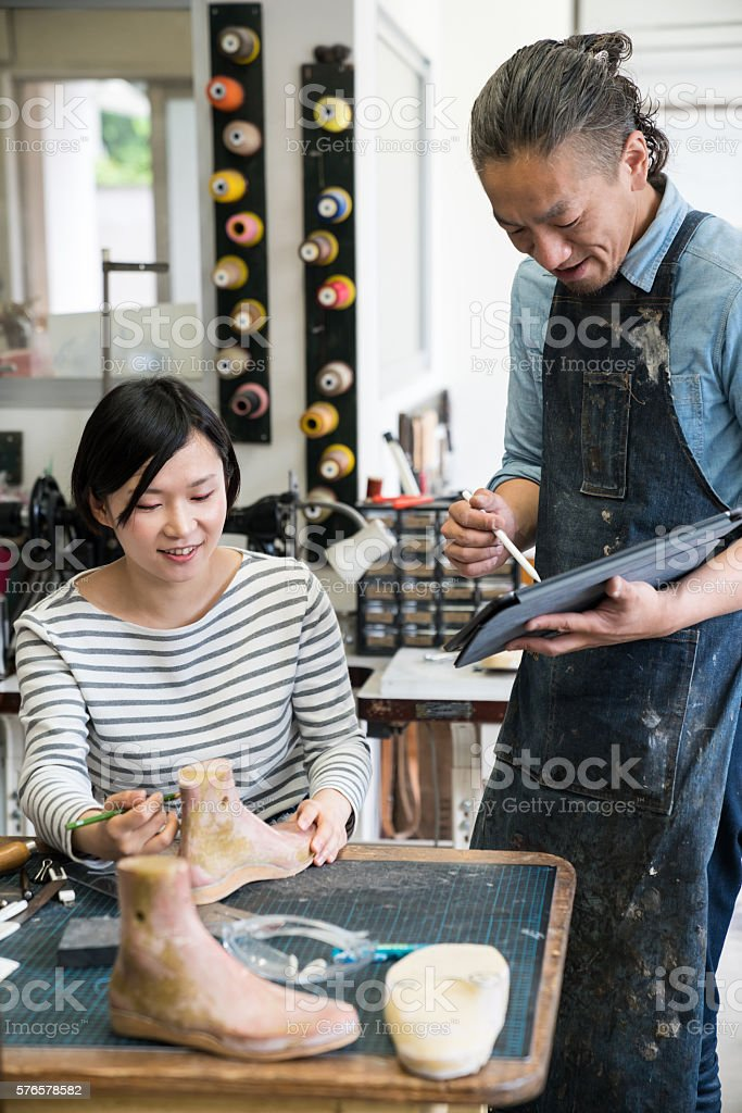 Cobblers discussing designs on digital tablet in their workshop stock photo
