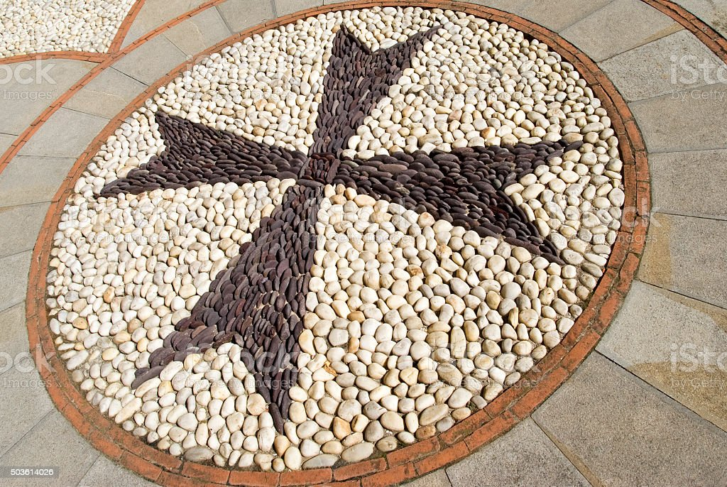Cobblestone pavement mosaic in the shape of a cross stock photo