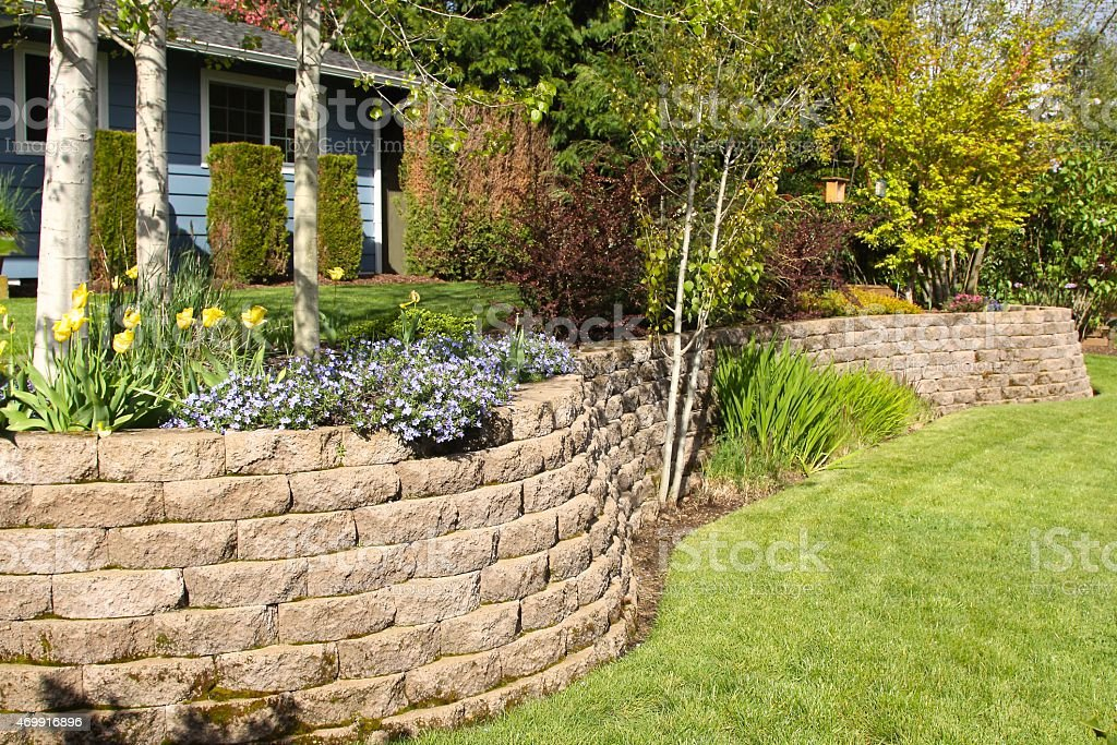 Cobblestone Retaining Wall In Landscaped Yard stock photo