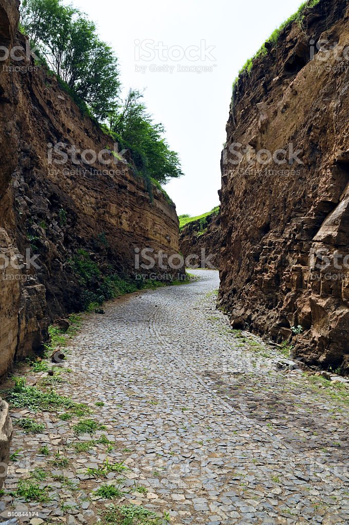 Cobblestone road between cliff stock photo
