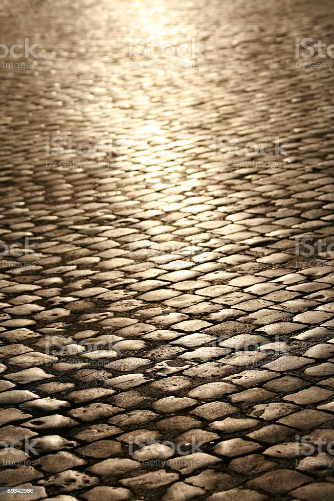 A cobblestone street with a light shining stock photo