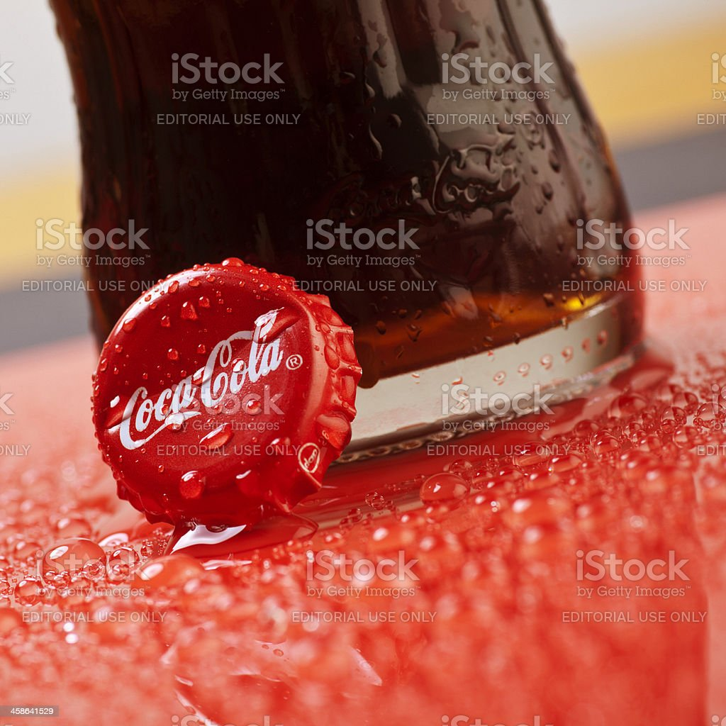 Coca Cola bottle cap on red and wet surface royalty-free stock photo