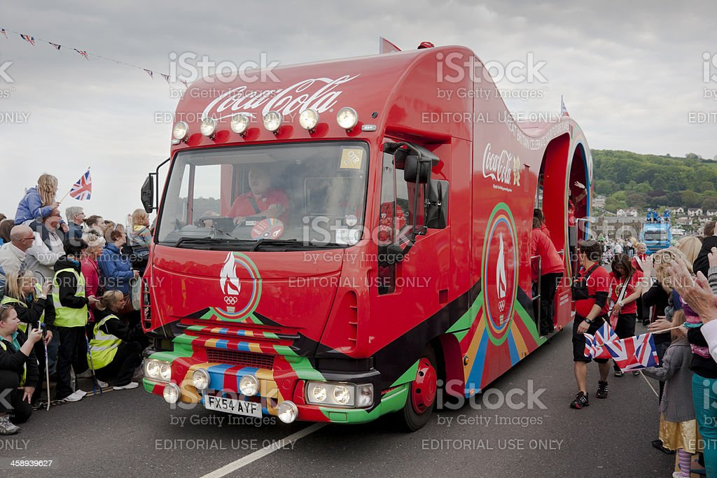 Coca Cola lorry in procession with the Olympic flame runners royalty-free stock photo
