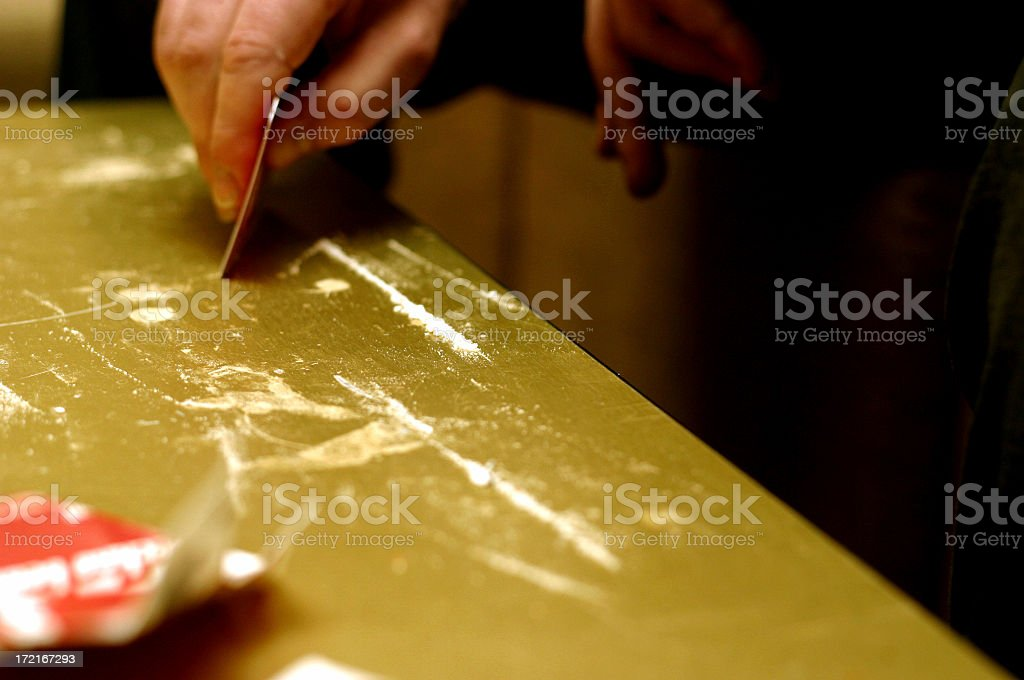 Cocaine addict preparing 2 lines of cocaine royalty-free stock photo