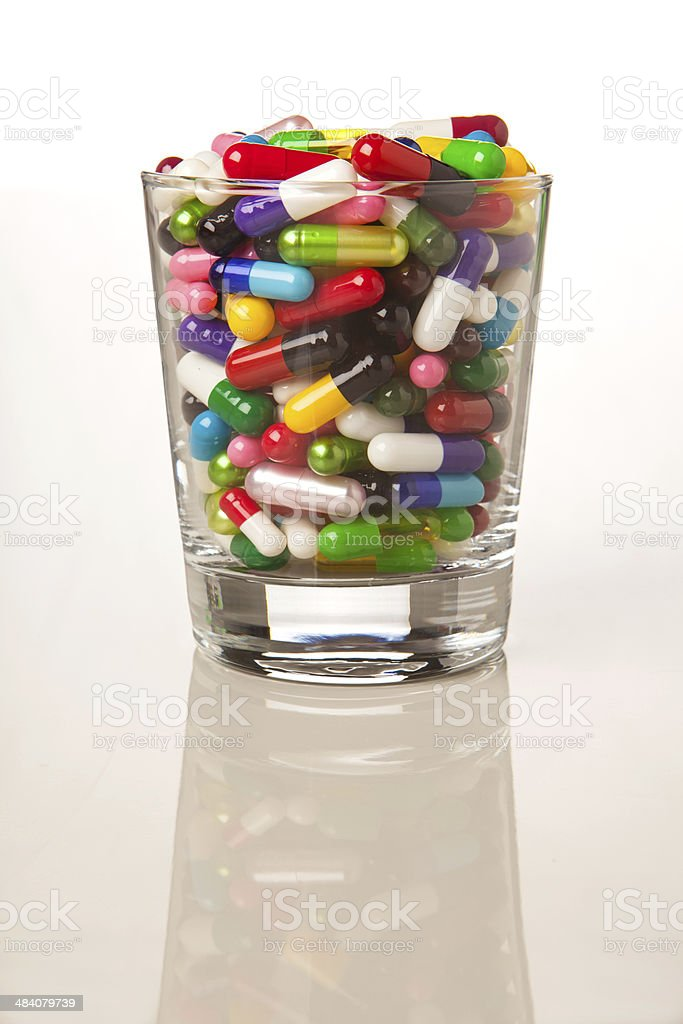 Cocktail glass filled with capsules and pills. royalty-free stock photo