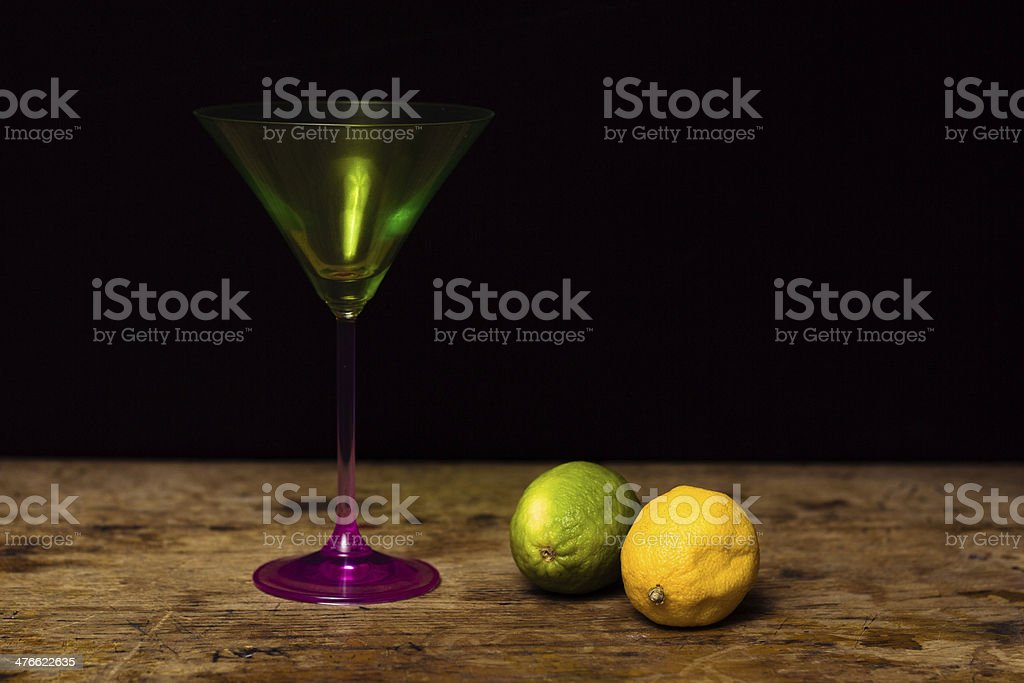 Cocktail glass, lemon and lime on wooden surface royalty-free stock photo