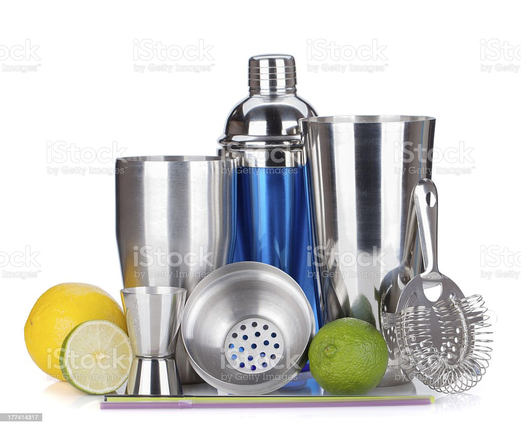 Cocktail shaker, strainer, measuring cup, drinking straws and citruses stock photo