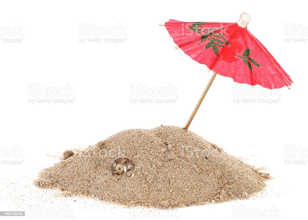Cocktail Umbrella in Sand Mound with Shells stock photo