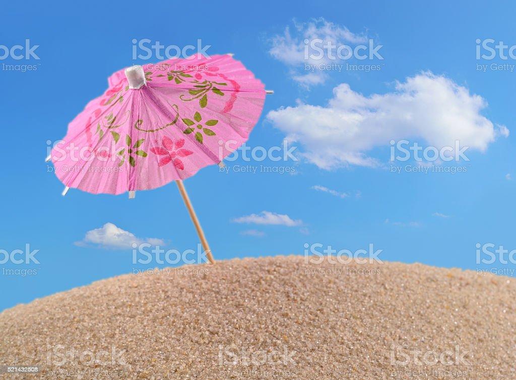 Cocktail umbrella on a beach sand stock photo
