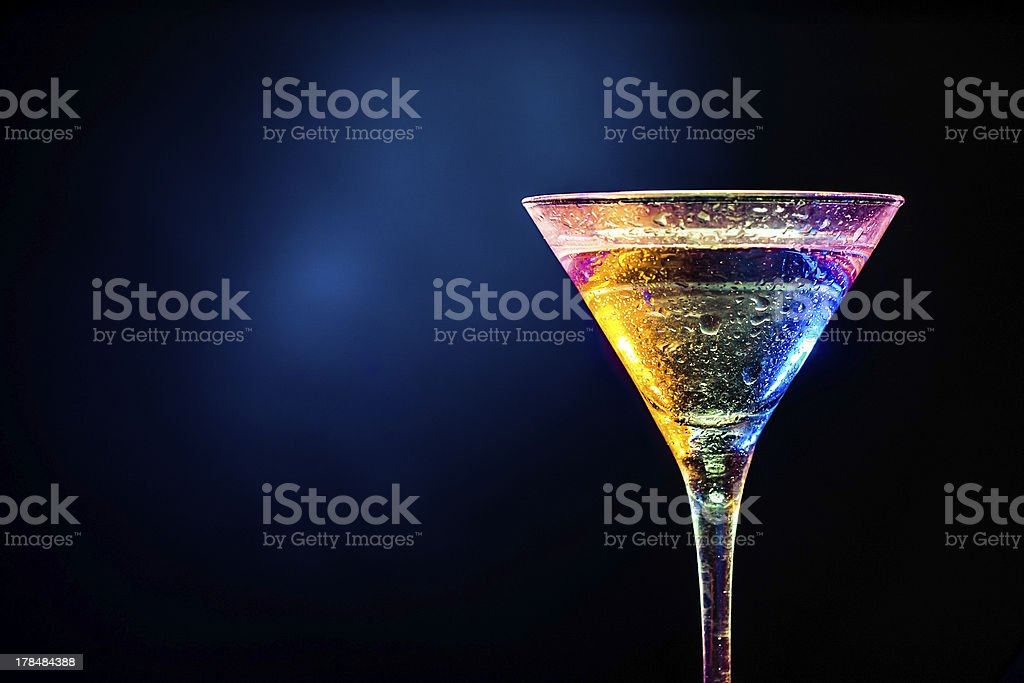 Cocktail with colorful exposure on dark background stock photo