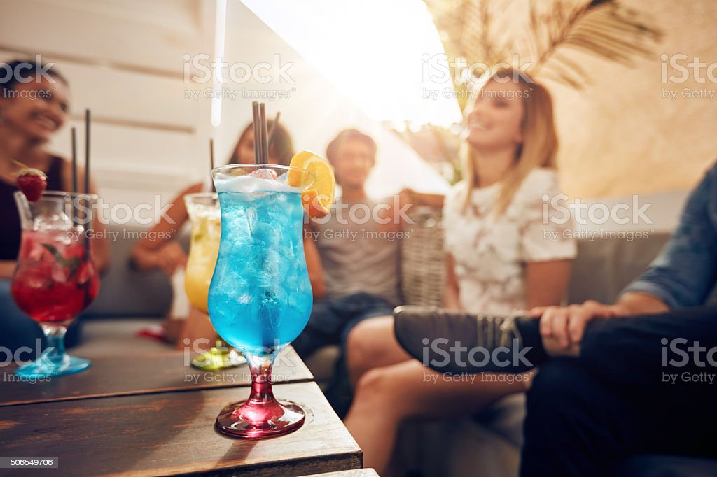 Cocktails on table with young people partying on rooftop stock photo