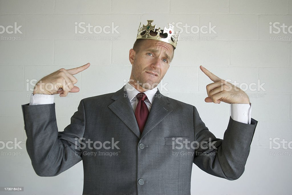 Cocky Businessman Pointing to Golden Crown Like He's the King stock photo