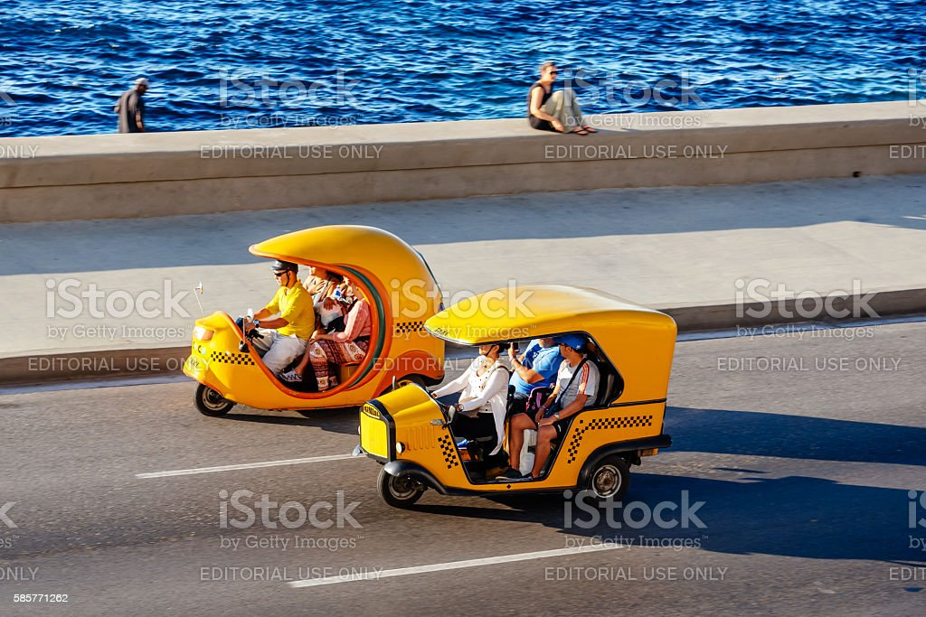 Coco Taxis driving along the Malecon in Havana, Cuba stock photo