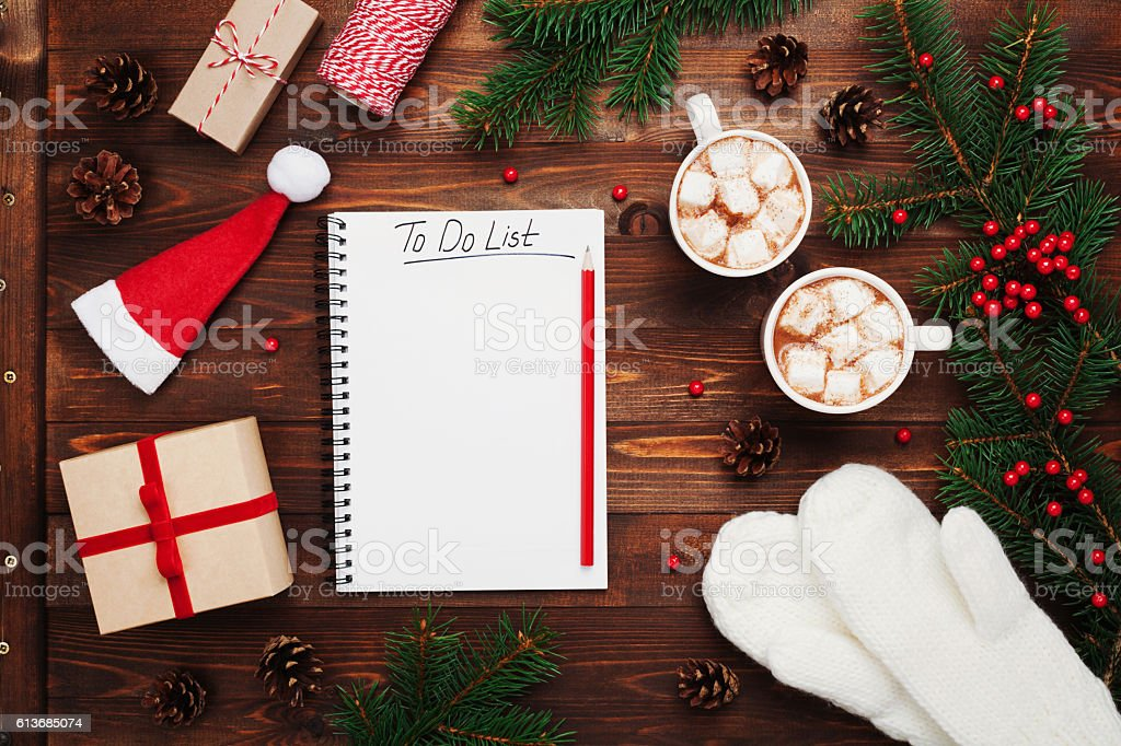 Cocoa or chocolate with gifts, mittens, christmas fir tree, notebook. stock photo