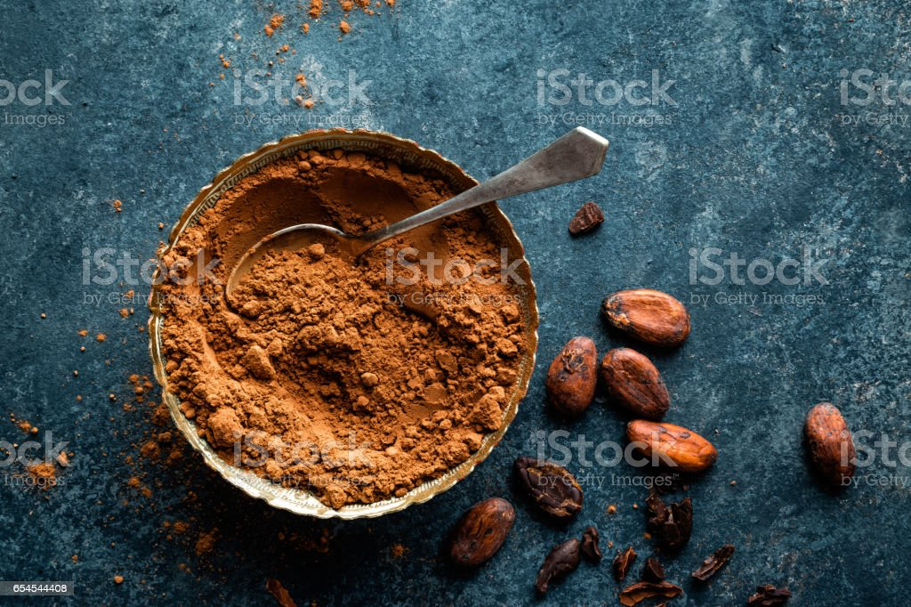 Cocoa powder and cacao beans on dark background, top view stock photo