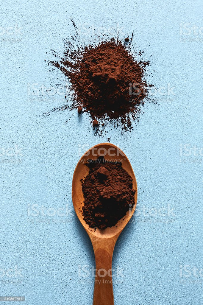 Cocoa powder in a wooden spoon stock photo