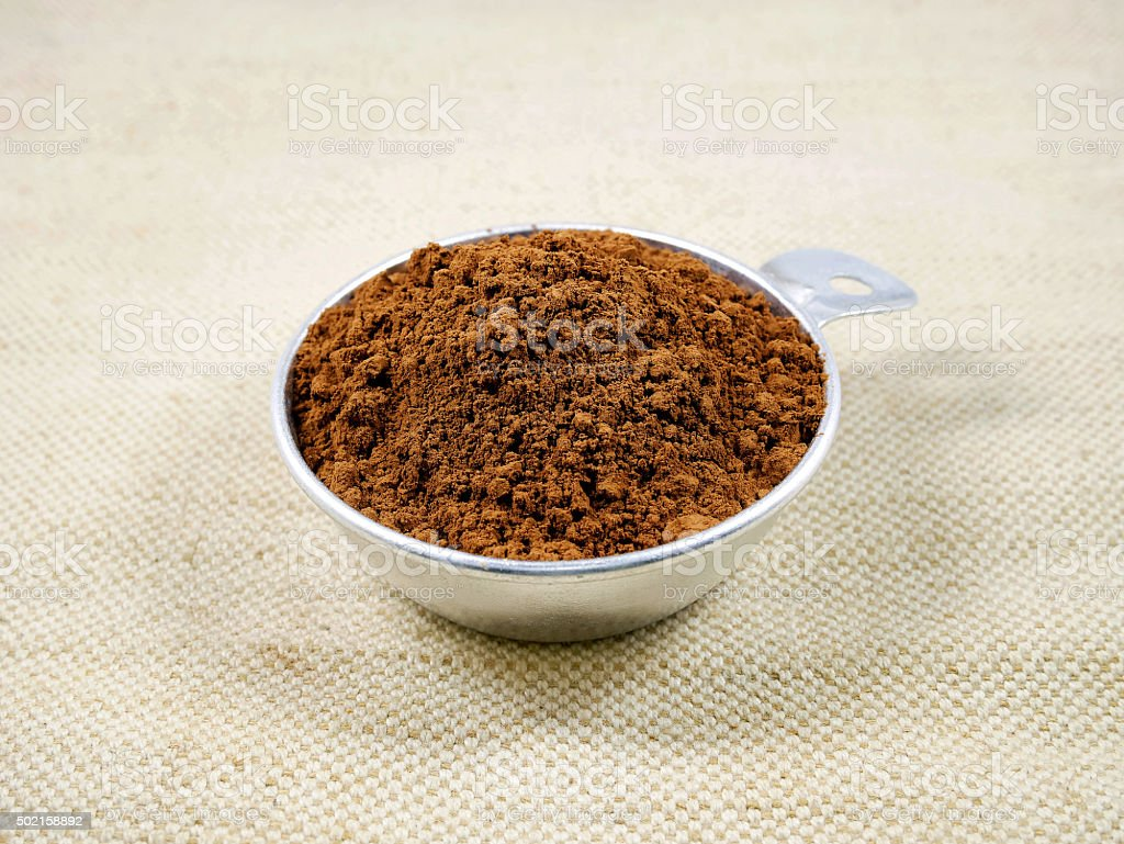 Cocoa powder in measuring cup stock photo