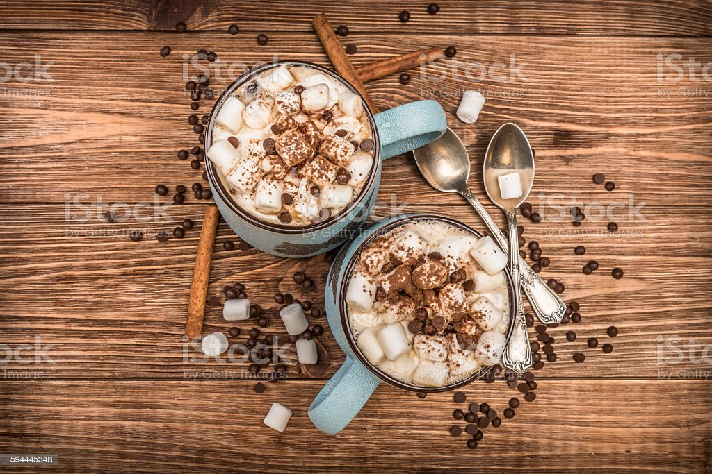 Cocoa with marshmallows and chocolate on a wooden table. stock photo