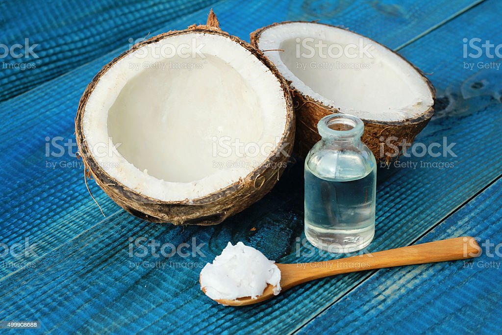 Coconut and coconut oil on blue rustic wooden background stock photo