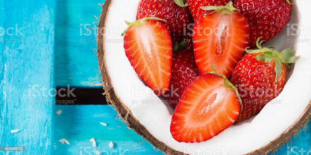 Coconut and strawberries on bright blue stock photo