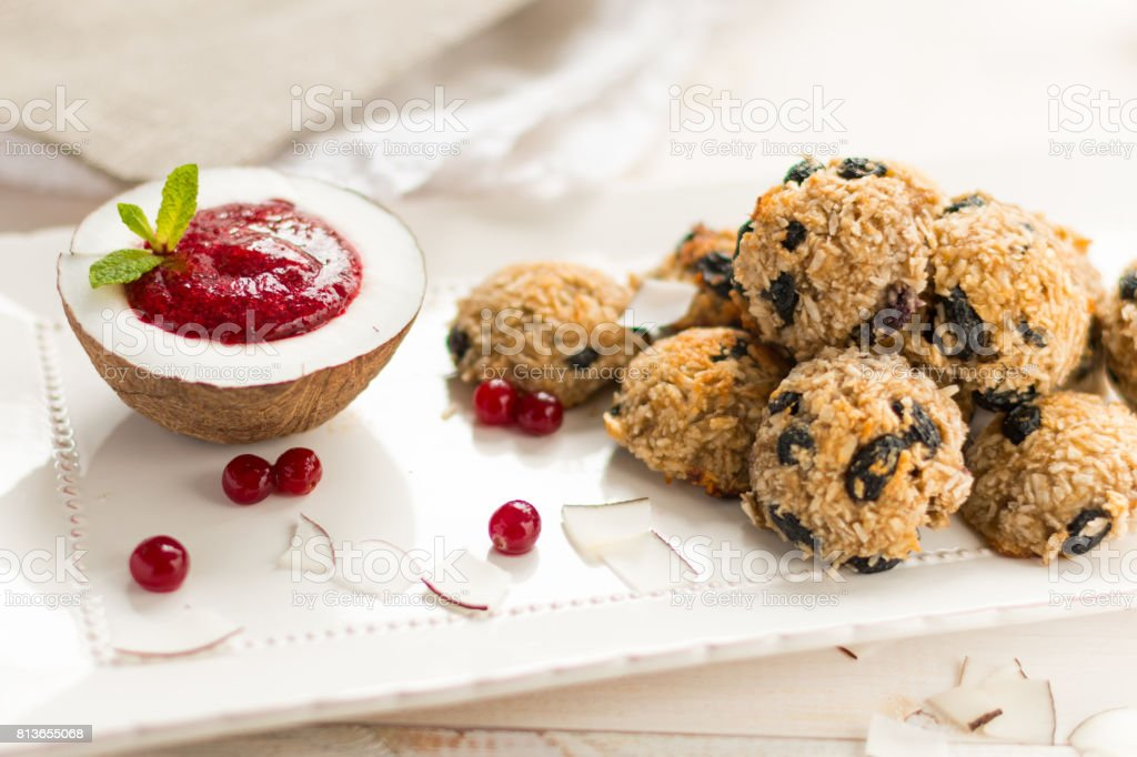 Coconut biscuits balls with cranberry sauce in coconut with mint on a white plate in a high key selective focus stock photo