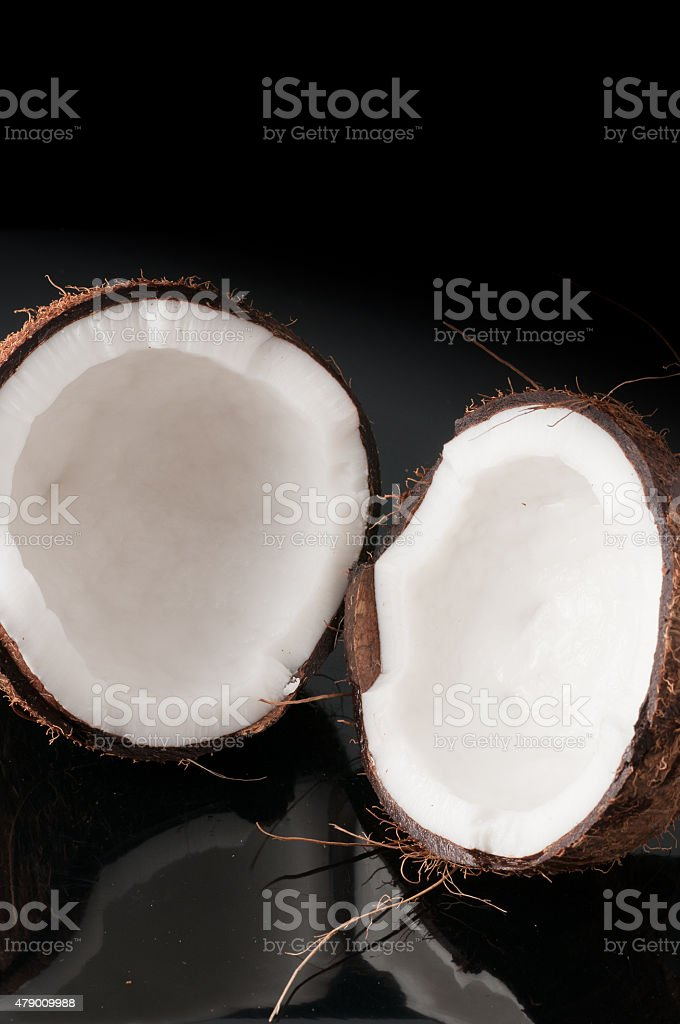Coconut broken in half on a black background