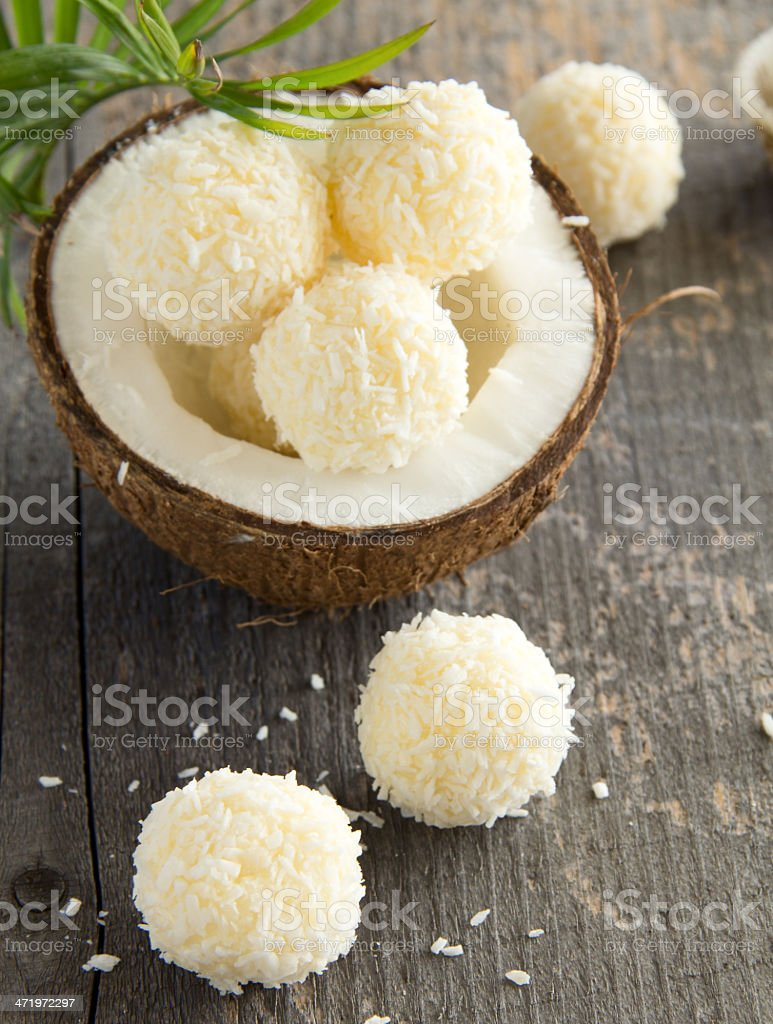 Coconut candy balls next to fresh coconut stock photo