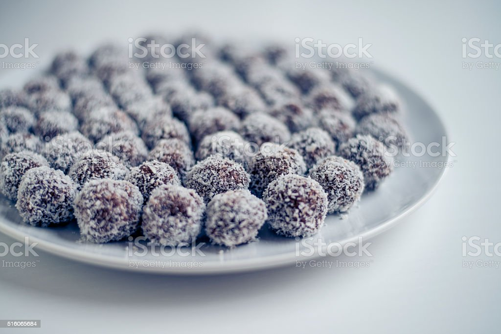 Coconut covered rum balls on a plate. stock photo