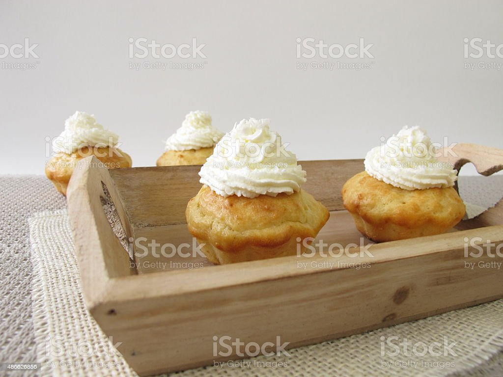 Coconut cupcakes with whipped cream on tray stock photo