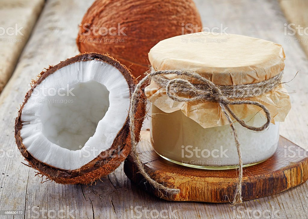 A coconut jar with coconut oil and coconuts sliced in half stock photo
