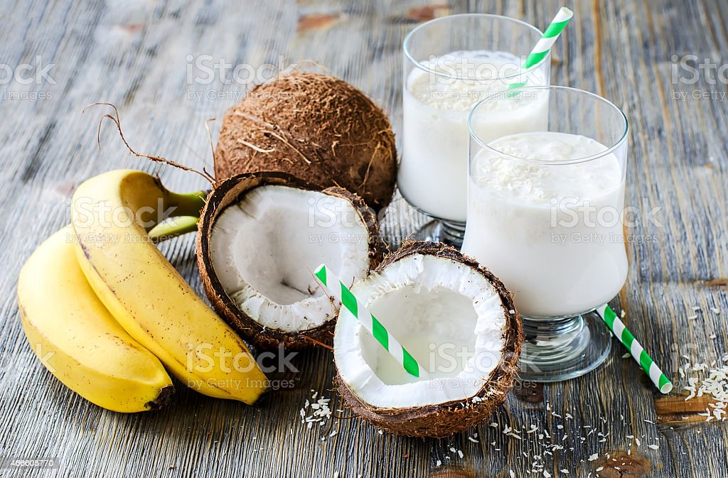 Coconut milk smoothie drink with bananas on wooden background stock photo