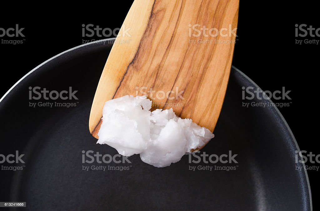 Coconut oil on wooden spatula over coated pan stock photo