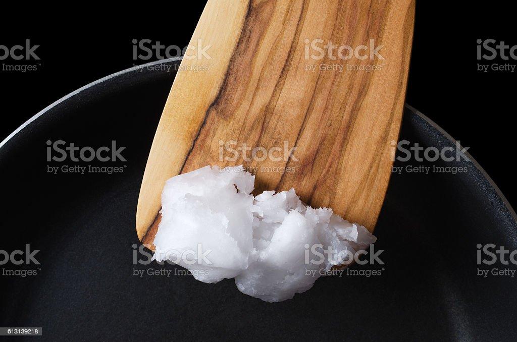 Coconut oil on wooden spatula over teflon pan stock photo