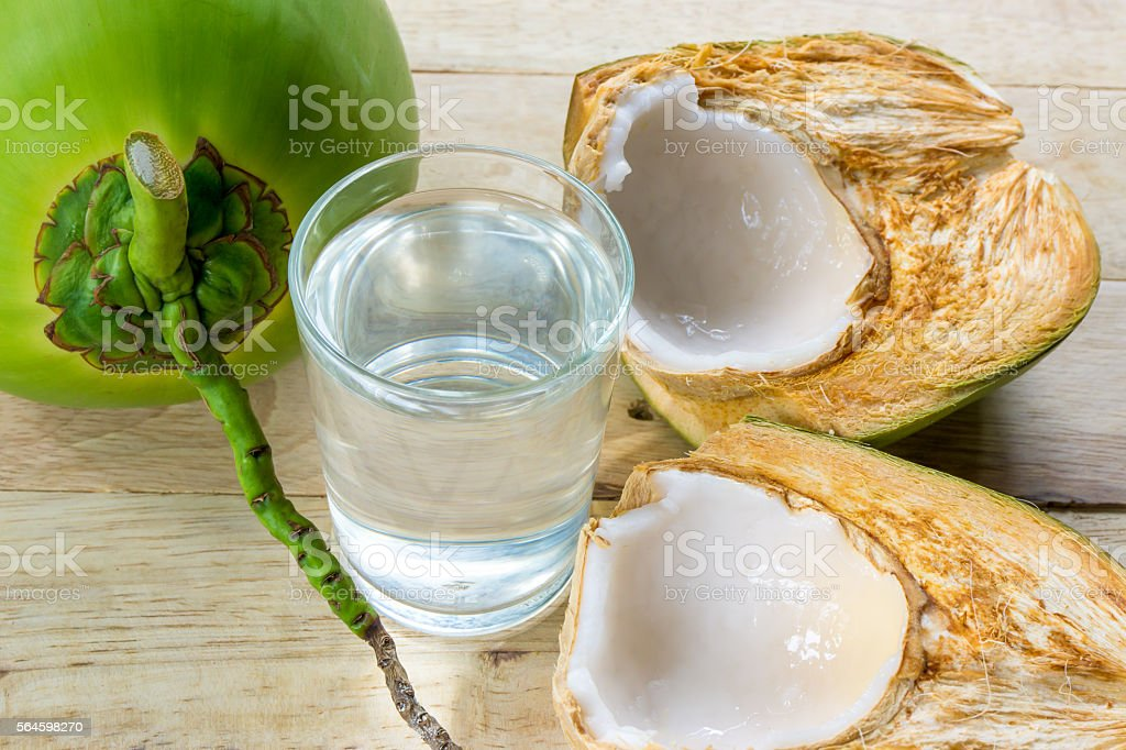 coconut water and fresh coconut on wooden background stock photo