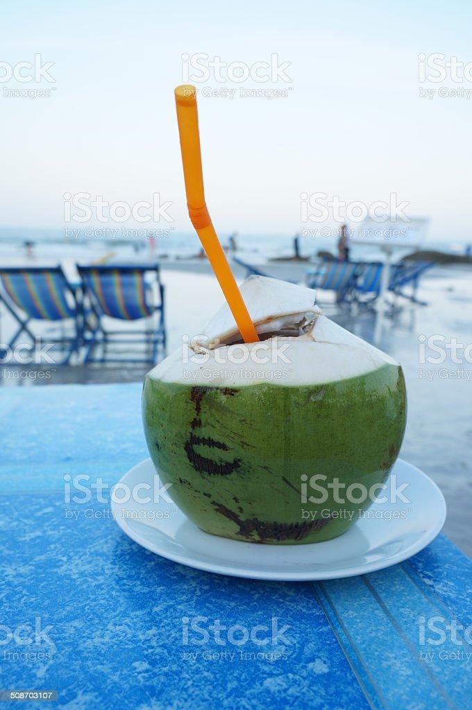 Cocco con un'arancia paglia sulla spiaggia foto stock royalty-free