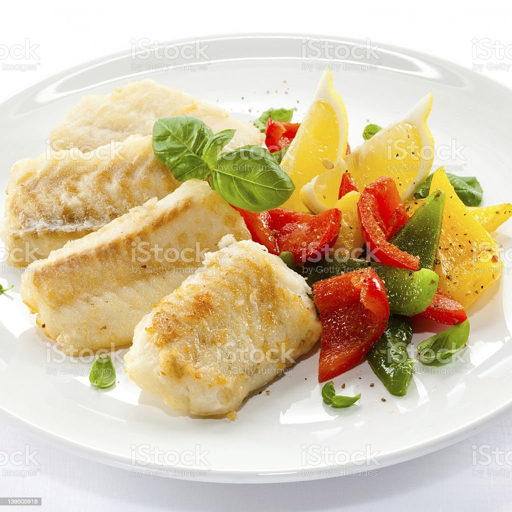 Cod filets surrounded by peppers and other vegetables stock photo