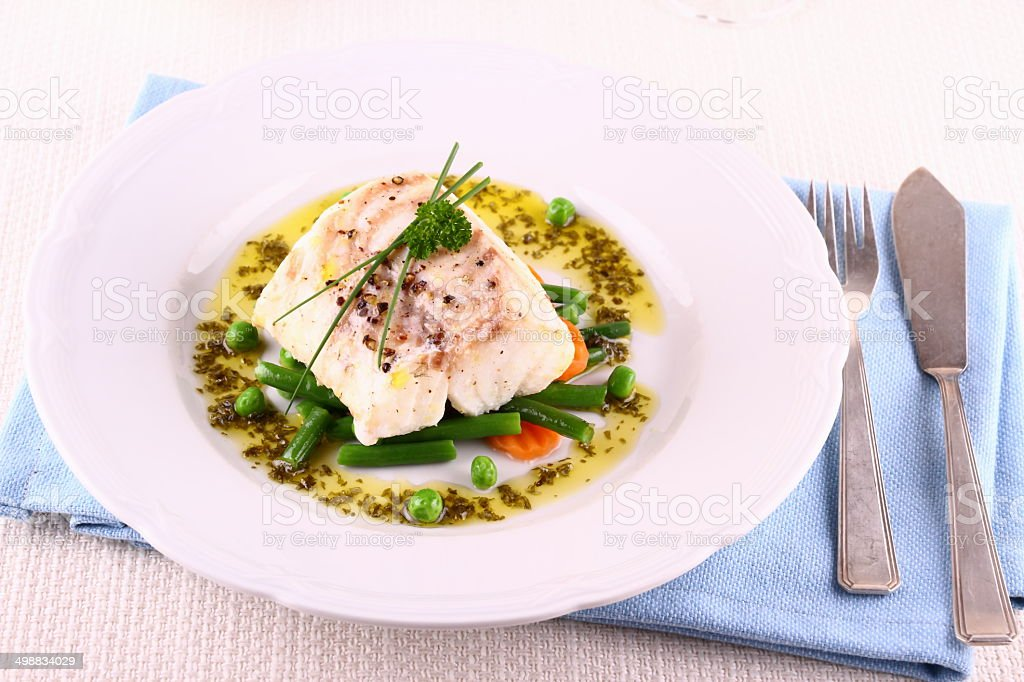 Cod fillet with green beans, peas, parsley, olive oil stock photo