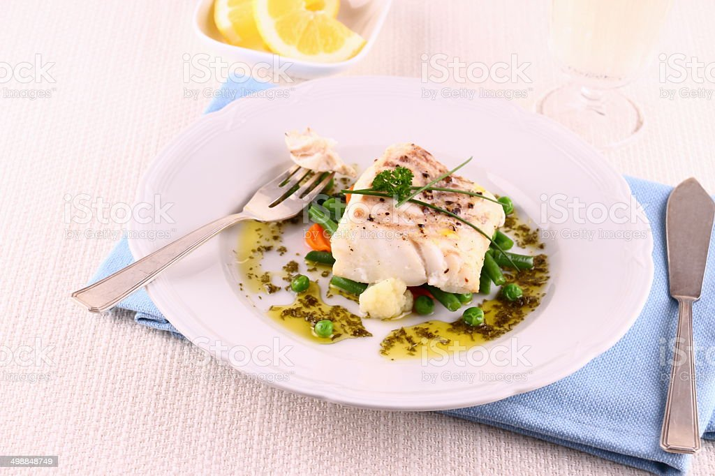 Cod fillet with green beans, peas, parsley, olive oil, wine stock photo