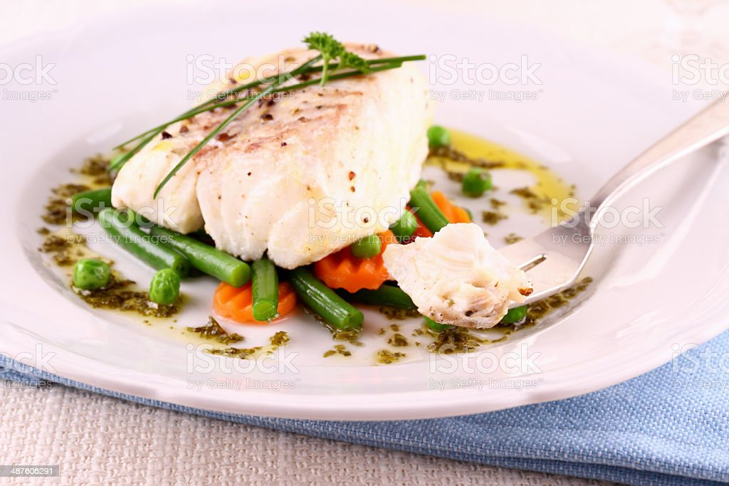 Cod Fillet with green beans, peas, parsley stock photo