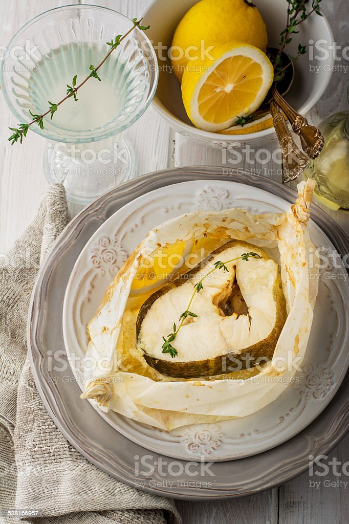 Cod fillets  baked in parchment paper with slices of lemon stock photo