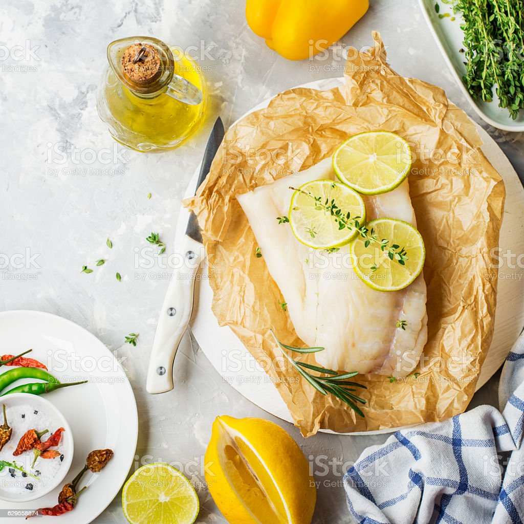 Cod fillets with vegetables before cooking in parchment paper stock photo