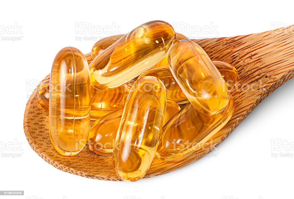 Cod liver oil omega 3 capsules on wooden spoon stock photo