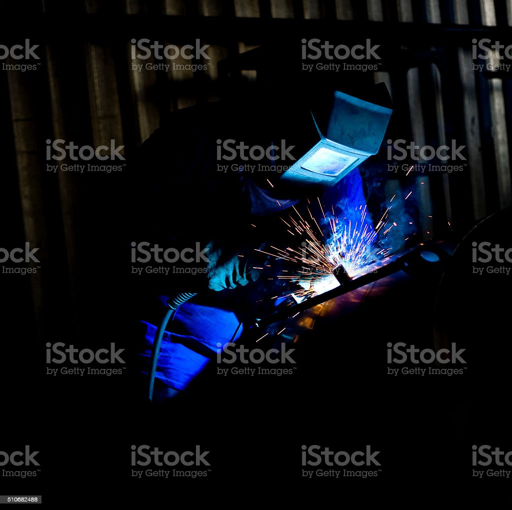 Coded welder with blue overalls stock photo