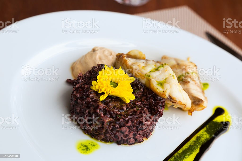 Codfish with black rice and sauce stock photo
