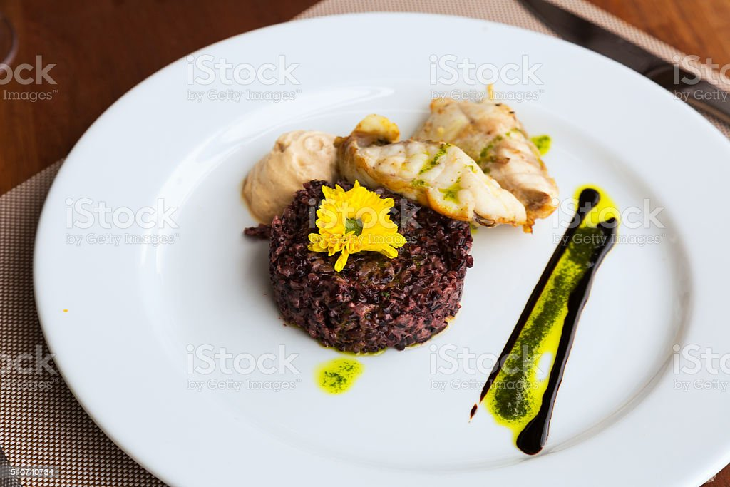 Codfish with black rice and sauce stock photo