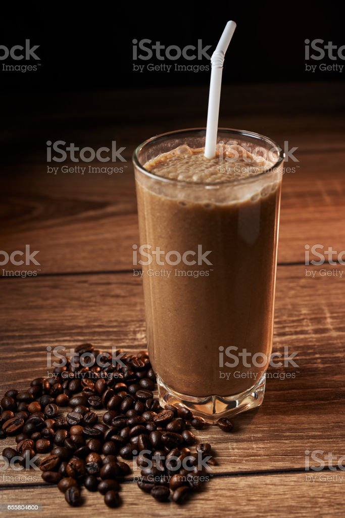 Coffee and banana smoothie in a glass on a wooden background stock photo