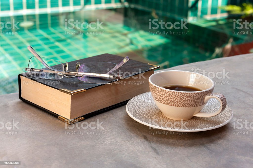 Coffee and book at pool royalty-free stock photo